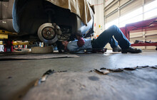 Mechanic Lays On A Trolley Under A Car In An Auto Repair Shop