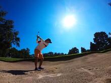 Full Length Of Man Playing Golf On Sand Against Sky