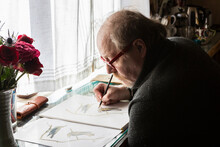 Mature Artist At Work Drawing On Paper, A Wildlife Study Of Birds.