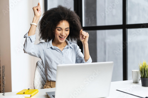 Fotografering Excited lucky mixed-race businesswoman raised fists up celebrating success, maki