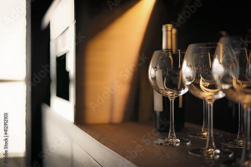 Fototapeta Close-up Of Wineglasses By Bottle In Shelf At Hotel Room obraz