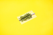 Marijuana Joint Made With Two Types Of Cannabis Preparations: Hashish And Weed Buds. High Quality Marijuana Joint Isolate On Yellow Background.