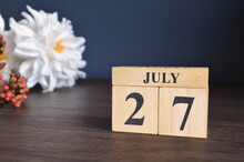 July 27, Date Cover Design With Calendar Cube And White Paeonia Flower On Wooden Table And Blue Background.