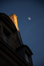Moon Over Chimney. Parisian Typical House With Mansard. Chimney In Golden Sunset Light And White Moon In Dark Blue Sky At Winter. Paris, France. Urban Romantics Concept. French Lifestyle Background.