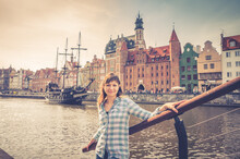 Young Girl Traveler With Checked Shirt Looking At Camera And Smile, Medieval Wooden Ship And Embankment Of Motlawa River With Old Buildings Houses In Gdansk City Historical Centre Background