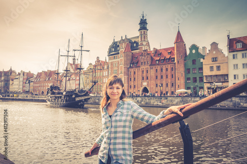 Young girl traveler with checked shirt looking at camera and smile, medieval woo Fototapeta