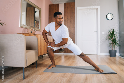 Front view of smiling strong African-American man doing side lunge exercise at home during working out standing on yoga mat at bright domestic room, looking away Wallpaper Mural