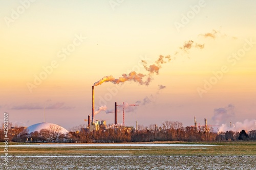 Foto industry complex in Frankfurt in late evening with  fields and smoking chimney