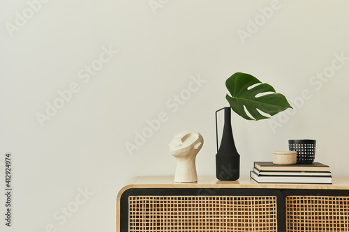 Modern scandinavian home interior with design wooden commode, tropical leaf in vase, books and personal accessories in stylish home decor. Template. Copy space. White walls.