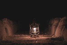 Burning Oil Lamp Stands On A Snowy Path At Night