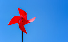 Red Toy Windmill On A Blue Sky Background, Summer Concept