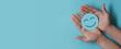 Leinwandbild Motiv Hand holding blue paper cut happy smile face, positive thinking, mental health assessment , world mental health day concept