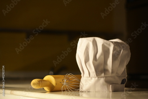 Fototapeta Close-up Of Chefs Hat With Wire Whisk And Rolling Pin On Table obraz