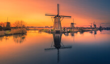 Traditional Windmill By Lake Against Sky During Sunset