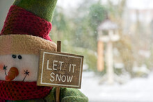 Snowman Doll With Let It Snow Sign. Snow Falling. Winter, Christmas Or Holiday Background.