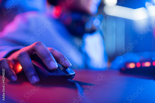 Fototapeta Professional cyber video gamer studio African American with personal computer armchair, keyboard for stream in neon color blur background. Soft focus obraz