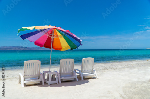 Foto Deck Chairs And Parasol At Beach Against Blue Sky