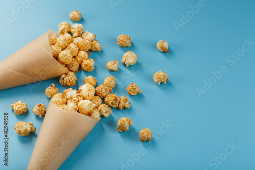 Fototapeta Caramel popcorn in a paper envelope on a blue background. obraz