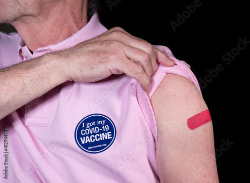 Senior adult man showing his adhesive plaster over his covid-19 vaccination with sticker saying he got his vaccine © steheap