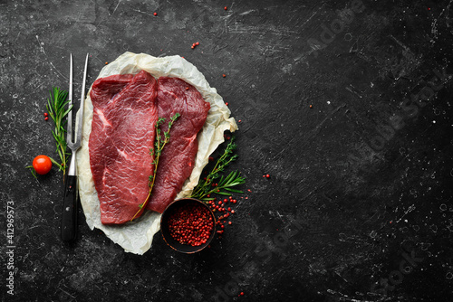 Fotografia Two raw veal steaks with rosemary and spices