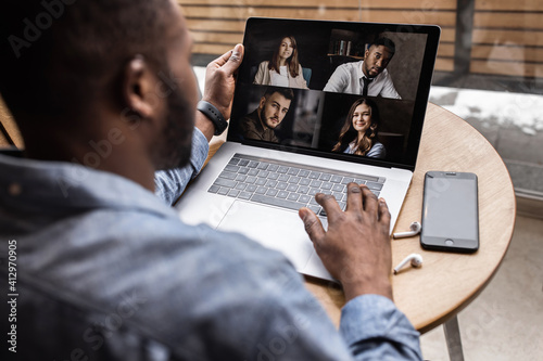 Obraz Back view. African-American worker discusses brainstorming video call with various colleagues, screen view of racial colleagues conducts team conference on webcam, participates in online briefing. - fototapety do salonu
