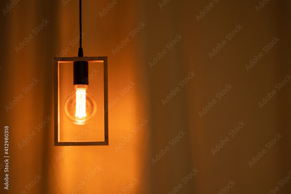 Fototapeta included electric light bulb on the background of dark curtains, lamp