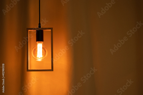 Fototapeta included electric light bulb on the background of dark curtains, lamp obraz