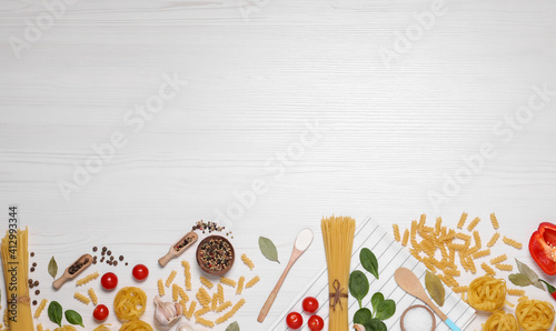 Fototapeta Flat lay composition with different types of pasta on white wooden table, space or text obraz
