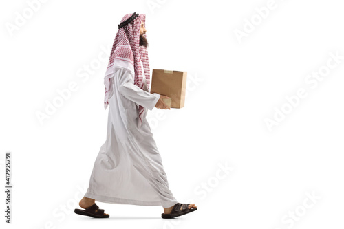 Slika na platnu Full length profile shot of a saudi arab man walking with a cardboard box
