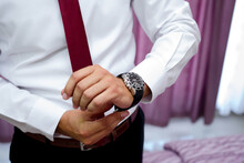 Closeup Of A Groom Wearing A White Shirt With A Red Tie And Getting Ready In A Room