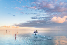 Early Morning, A Boat Heads Out On The Ocean On A Fishing Trip In The Florida Keys As The Sun Rises. The Ocean Is Calm And Flat There Are A Few Clouds In The Sky.