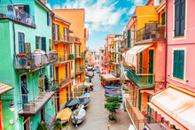 Manarola, Liguria Italy. Traditional Typical Italian Village In National Park Cinque Terre, Colorful Multicolored Buildings Houses, Fishing Boats On Road, Blue Cloudy Sky