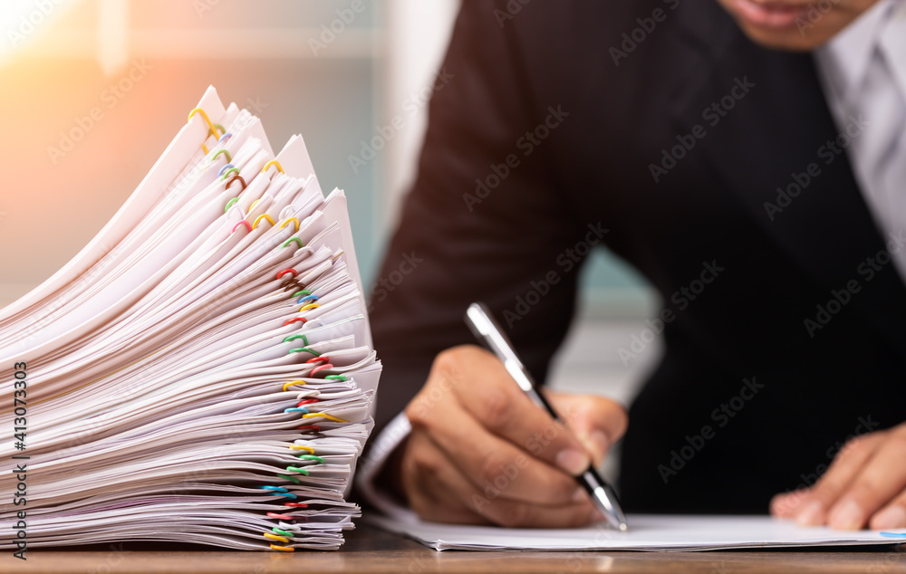 Fototapeta Male office workers holding and writing documents on office desk with light fair, Stack of business overload paper and paperless concept.