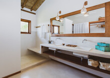 Modern Luxury Summer Holiday Or Vacation Wooden Beach House Toilet Interior With White Walls, A Large Mirror And Wooden Ceiling.