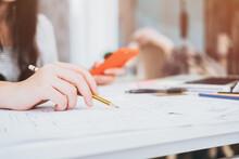 Cropped Image Of Female Architect Working On Blueprint At Workshop