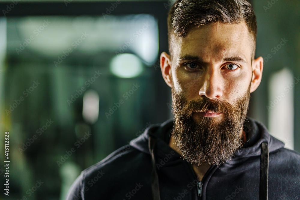 Fototapeta Front view close up portrait of young adult caucasian man with dark hair and beard in black shirt hoodie looking to the camera in dark - Confident modern male dramatic portrait with copy space