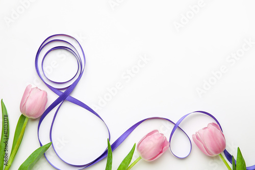 Fototapeta Figure 8 made of violet ribbon and tulip flowers on light background. International Women's Day celebration obraz