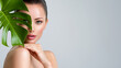 canvas print picture - Beautiful woman with green leave near face and body.  Closeup girl's face with green leave. Skin care beauty treatments concept.