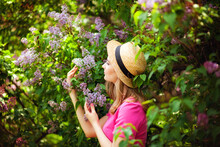 A Young Woman Enjoys The Smell Of Lilac On A Sunny Summer Day. Aromatherapy And The Concept Of Spring. A Beautiful Woman In A Pink Vintage Dress And A Straw Hat Stands In A Lilac Garden.
