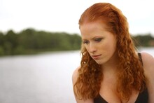 Thoughtful Beautiful Woman Looking Down Against Lake
