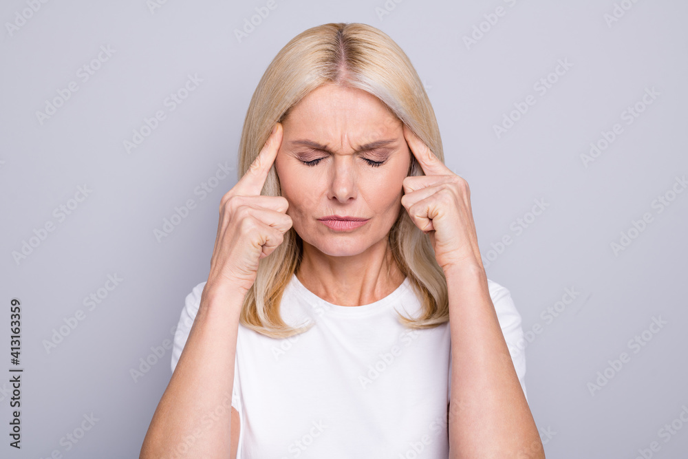 Fototapeta Portrait of blond stressed old lady hands head wear white cloth isolated on grey color background