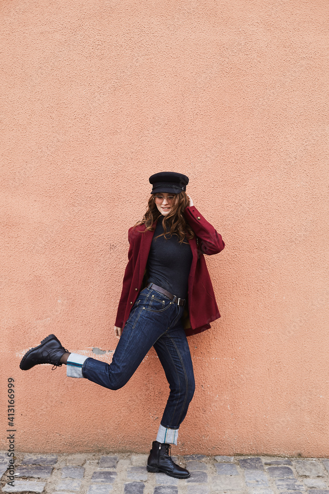 Fototapeta Beautiful and stylish young woman in cap, red coat and sunglasses posing in front of the beige wall