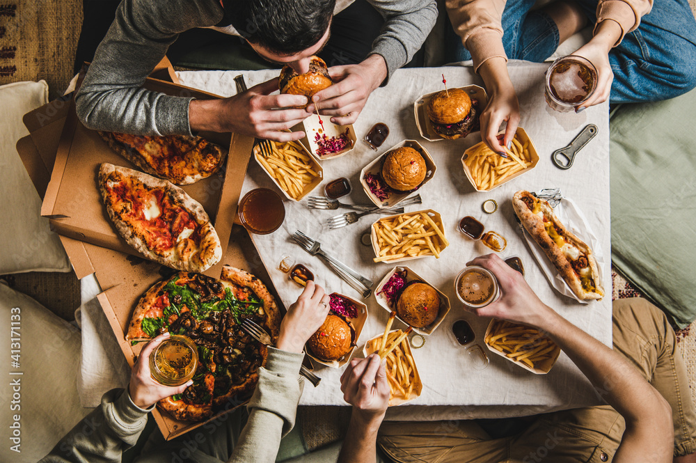 Fototapeta Lockdown fast food dinner from delivery service. Flat-lay of friends sitting and having beer quarantine party with burgers, french fries, sandwiches, pizza and salad over table background, top view
