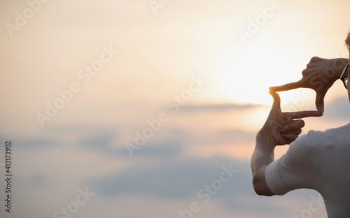 Fototapeta Midsection Of Person Making Finger Frame Against Sky During Sunset obraz