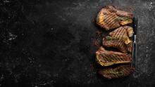 Variety Of Grill Black Angus Prime Meat Steaks: T-bone, Striploin, Rib Eye, New York Steak. Top View. Rustic Style.