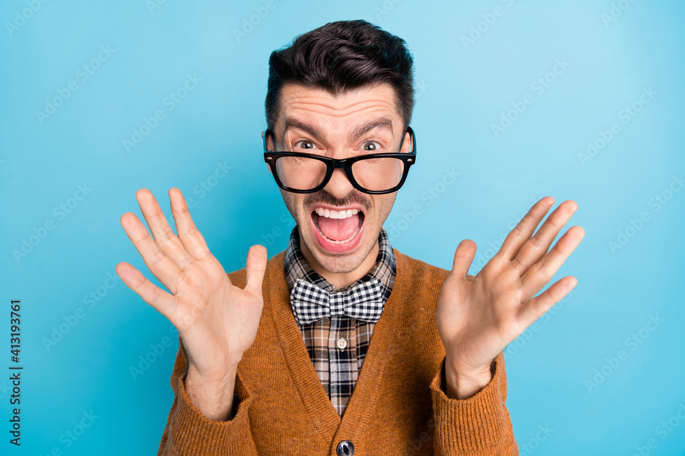 Fototapeta Photo of crazy angry young man scream loud raise palms wear plaid bow tie isolated on blue color background