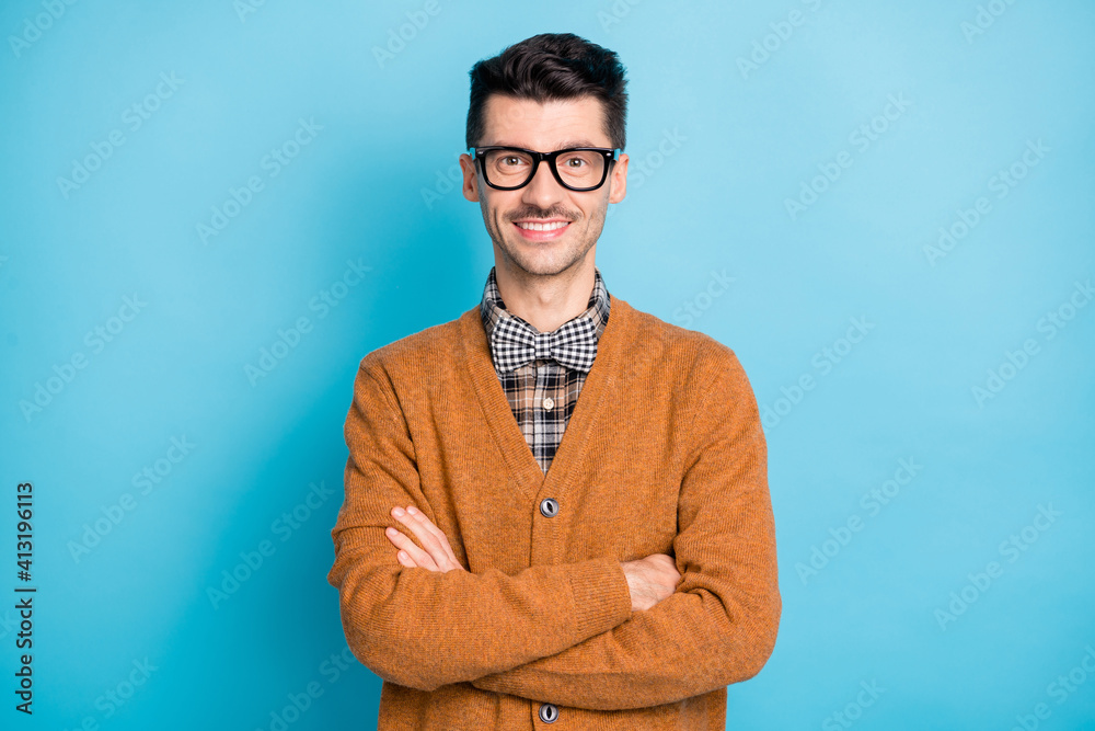 Fototapeta Photo of cheerful funny young man hand wear brown cardigan spectacles arms crossed isolated blue color background