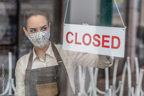 Unhappy waitress wearing face mask turns a sign closed in a bar due to coronavirus