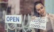 canvas print picture - As Covid-19 restrictions ease, restaurant owner unsticks the closure sign putting open sign on a window