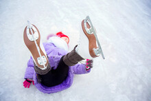 A Girl, Shod In Figure Skates, Lies On The Ice With Her Legs Raised, Focus On Skates
